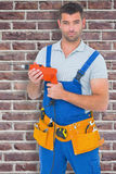 Composite image of confident male carpenter in overall holding drill machine Stock Photo