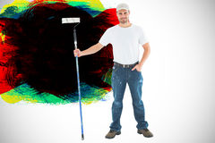 Composite image of confident man holding paint roller on white background Stock Photography