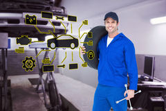 Composite image of confident mechanic carrying tire. Confident mechanic carrying tire against auto repair shop Royalty Free Stock Images
