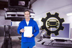 Composite image of confident mechanic showing blank clipboard Royalty Free Stock Images