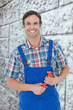Composite image of confident plumber holding monkey wrench Royalty Free Stock Images