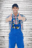 Composite image of confident plumber showing thumbs up sign Royalty Free Stock Image