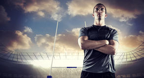 Composite image of confident rugby player with arms crossed Stock Image
