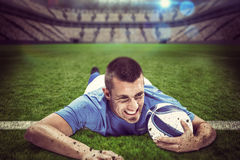 Composite image of confident rugby player lying in front with ball Royalty Free Stock Photography