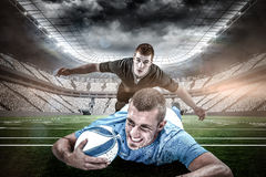 Composite image of confident rugby player lying in front with ball Stock Photo