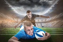 Composite image of confident rugby player lying in front with ball Royalty Free Stock Photo