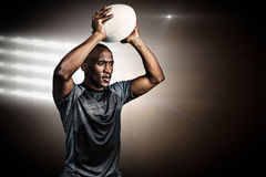 Composite image of confident sportsman throwing rugby ball Stock Images
