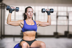 Composite image of confident woman lifting dumbbells Royalty Free Stock Image