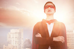 Composite image of confident woman pretending to be super hero stock images