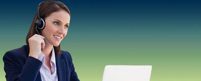 Composite image of confident woman wearing headset using laptop at desk Royalty Free Stock Photo
