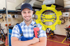 Composite image of confident young male repairman holding adjustable spanner. Confident young male repairman holding adjustable spanner against workshop Royalty Free Stock Photos