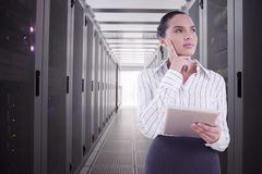 Composite image of confused businesswoman using a tablet pc. Confused businesswoman using a tablet pc against data center Stock Images