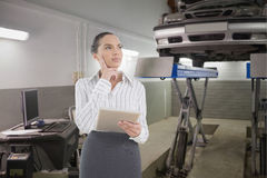 Composite image of confused businesswoman using a tablet pc Royalty Free Stock Image
