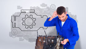 Composite image of confused mechanic repairing car engine. Confused mechanic repairing car engine against grey vignette royalty free stock photography