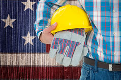 Composite image of construction worker holding hard hat and gloves Royalty Free Stock Images