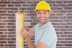 Composite image of construction worker using measure tape to mark on plank. Construction worker using measure tape to mark on plank against red brick wall royalty free stock photo