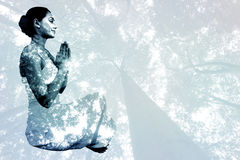 Composite image of content brunette in white sitting in lotus pose Stock Photos