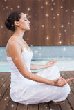 Composite image of content brunette in white sitting in lotus pose Royalty Free Stock Images
