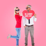 Composite image of cool couple holding a red heart together Stock Photos