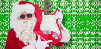 Composite image of cool santa showing electric guitar. Cool santa showing electric guitar against knitting christmas background snowflakes royalty free stock image