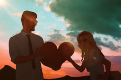 Composite image of cool young couple holding red heart Royalty Free Stock Image