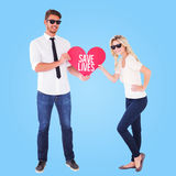 Composite image of cool young couple holding red heart Stock Image