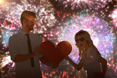 Composite image of cool young couple holding red heart. Cool young couple holding red heart against colourful fireworks exploding on black background Stock Photos