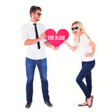 Composite image of cool young couple holding red heart Stock Photo