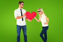 Composite image of cool young couple holding red heart Stock Images