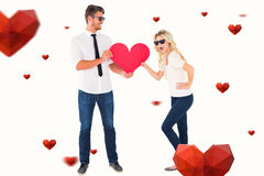 Composite image of cool young couple holding red heart. Cool young couple holding red heart against hearts royalty free stock photo