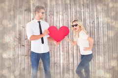 Composite image of cool young couple holding red heart Royalty Free Stock Photography