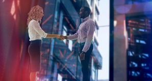 Composite image of corporate man and woman doing handshake Royalty Free Stock Photos