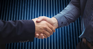 Composite image of corporate men shaking hands. Corporate men shaking hands against shiny lines on black background Royalty Free Stock Photography