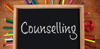 Composite image of counselling text against white background. Counselling text against white background against high angle view of empty chalkboard with colorful stock photography