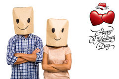 Composite image of couple with arms crossed wearing smiley paper bags Stock Photos