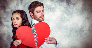 Composite image of couple back to back holding heart halves. Couple back to back holding heart halves against grey background Stock Photos