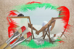Composite image of couple on the beach in deck chairs Stock Photo