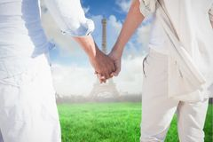 Composite image of couple on the beach looking out to sea holding hands Stock Photography