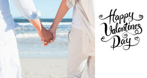 Composite image of couple on the beach looking out to sea holding hands. Couple on the beach looking out to sea holding hands against happy valentines day Stock Image