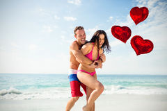 Composite image of couple on beach and love heart balloons 3d. Love heart balloons against playful couple enjoying on beach 3d Stock Photography