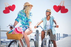 Composite image of couple on bike ride by the beach Stock Photos