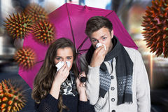 Composite image of couple blowing nose while holding umbrella. Couple blowing nose while holding umbrella against blurry new york street royalty free stock photography
