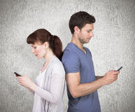 Composite image of couple both sending text messages. Couple both sending text messages against weathered surface Royalty Free Stock Photography