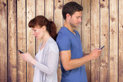 Composite image of couple both sending text messages. Couple both sending text messages against wooden planks Royalty Free Stock Photography