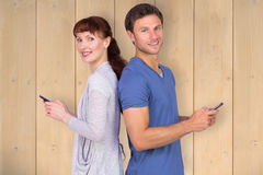 Composite image of couple both sending text messages. Couple both sending text messages against wooden planks Stock Photos