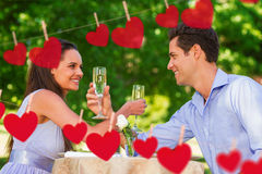 Composite image of couple with champagne flutes sitting at outdoor café. Couple with champagne flutes sitting at outdoor café against hearts hanging on a line Royalty Free Stock Photos