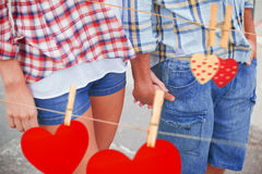 Composite image of couple in check shirts and denim holding hands Stock Photo