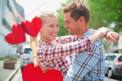 Composite image of couple in check shirts and denim hugging each other Royalty Free Stock Photo