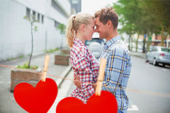 Composite image of couple in check shirts and denim hugging each other Royalty Free Stock Image