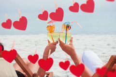 Composite image of couple clinking glasses of cocktail on beach Stock Image